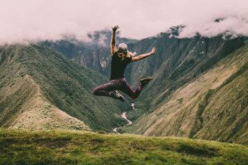 Kvinna hoppar av glädje när hon nått toppen av ett berg